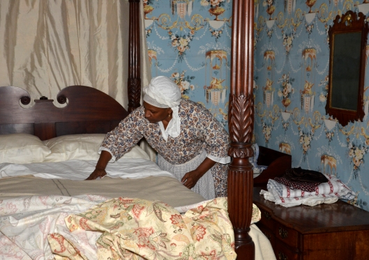 Goody Morris makes up a bed. Photograph by J. D. Kay