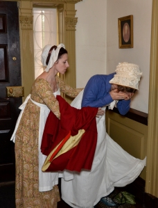 Mary assists Alice in the hallway as she prepares to face her mother. Photograph by J. D. Kay