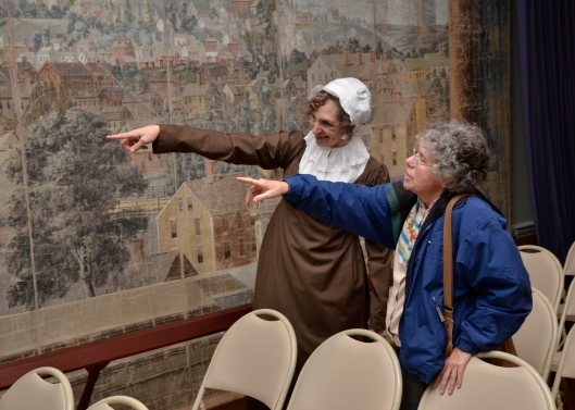 Mrs Pabodie points out East Side landmarks to a visitor examining the theatre curtain backdrop painted around 1810. Photo by J. D. Kay