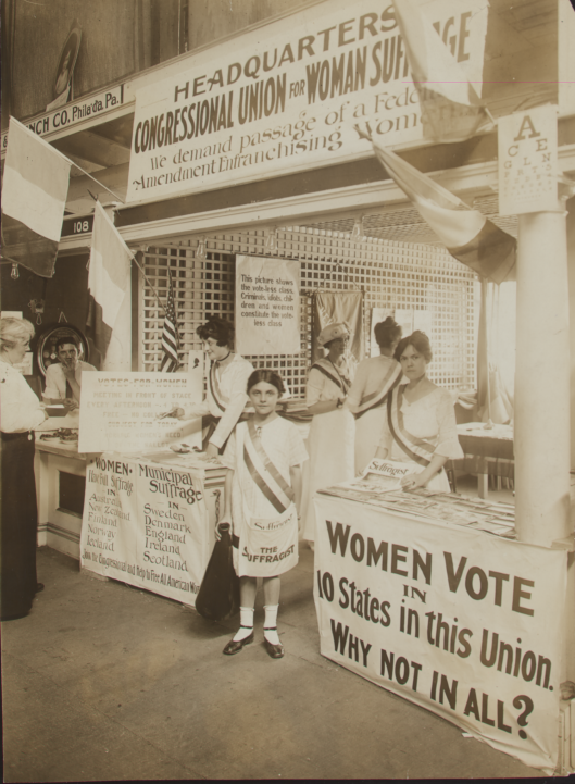 girl in front of suffrage signs